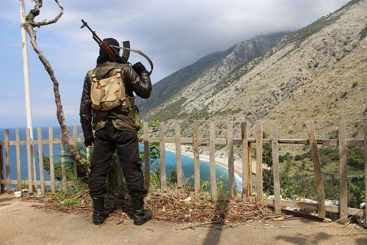 A Syrian rebel fighter stands on a ridge overlooking the Mediterranean Sea.