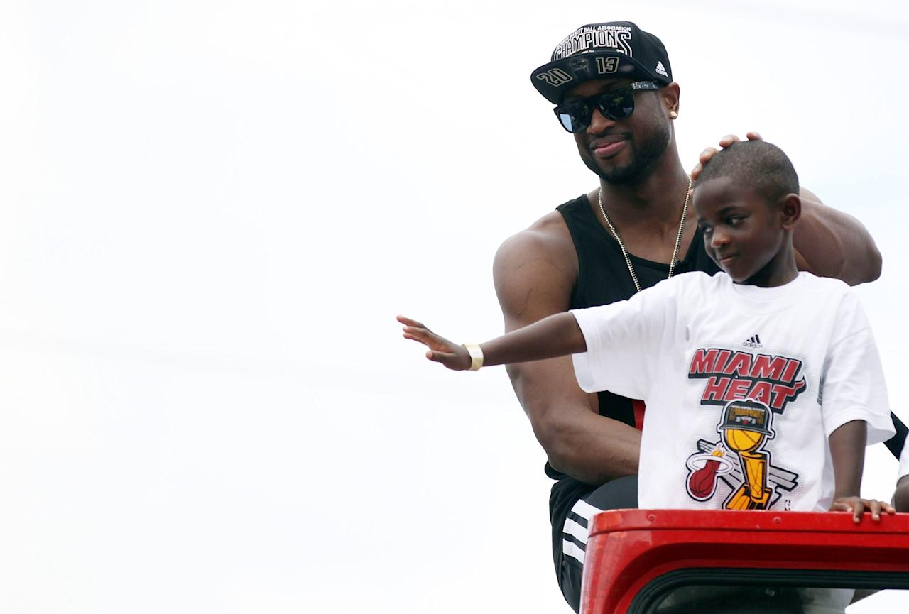 MIAMI, FL - JUNE 24: Guard Dwyane Wade #3 of the Miami Heat rides a bus with his son during the Championship victory parade on the streets on June 24, 2013 in Miami, Florida. The Miami Heat defeated the San Antonio Spurs in the NBA Finals. (Photo by Marc Serota/Getty Images)