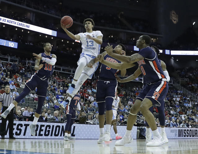<p>North Carolina's Cameron Johnson (13) heads to the basket as Auburn's Samir Doughty, left, Chuma Okeke and Horace Spencer, right, defend during the first half of a men's NCAA tournament college basketball Midwest Regional semifinal game Friday, March 29, 2019, in Kansas City, Mo. (AP Photo/Charlie Riedel) </p>