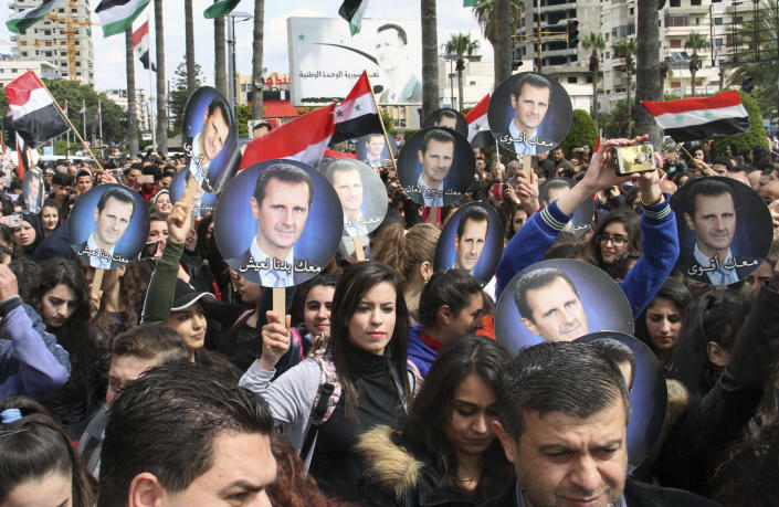 FILE - In this March. 27, 2019, file photo released by the Syrian official news agency SANA, people hold Syrian flags and portraits of President Bashar Assad during a protest against U.S. President Donald Trump's move to recognize Israeli sovereignty over the Israeli occupied Golan Heights, in the costal port city of Tartus, Syria. Assad has snapped up a prize from world powers that have been maneuvering in his country's multifront wars. Without firing a shot, his forces are returning to towns and villages in northeastern Syria where they haven't set foot for years. (SANA via AP, File)