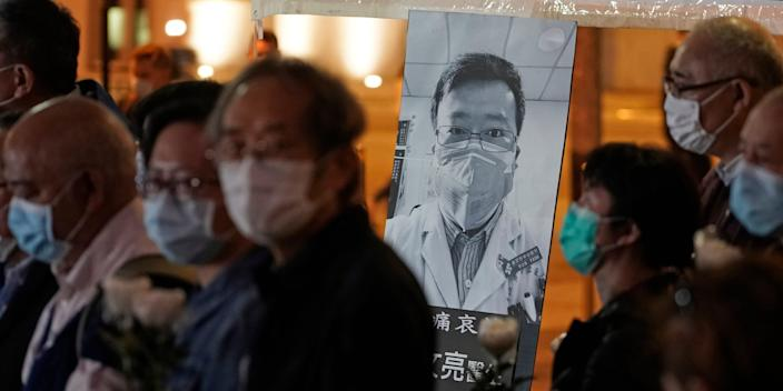 People wearing masks, attend a vigil for Chinese doctor Li Wenliang, in Hong Kong, Friday, Feb. 7, 2020. The death of a young doctor who was reprimanded for warning about China's new virus triggered an outpouring Friday of praise for him and fury that communist authorities put politics above public safety. (AP Photo/Kin Cheung)