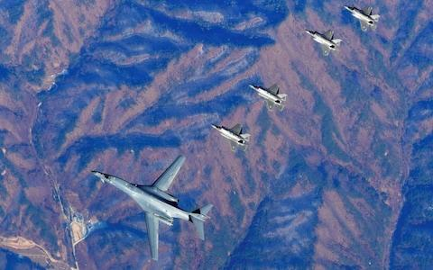 This handout taken and released by the South Korean Defence Ministry in Seoul on December 6, 2017 shows a US Air Force B-1B Lancer bomber (C), two US F-35A and two US F-35B stealth jets (top) flying over South Korea with South Korea's two F-16 and two F-15K fighter jets (bottom) during a joint military drill. - Credit: AFP/Handout