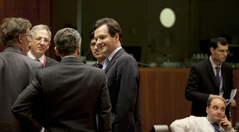 British Finance Minister George Osborne, center, speaks with Italian Economy Minister Vittorio Grilli, third left, during a meeting of EU finance ministers in Brussels on Tuesday, March 5, 2013. European Union finance ministers were expected Tuesday to give wide political approval to capping bankers' bonuses, with Britain being the only country of the 27-nation bloc staunchly opposing the measure, diplomats said. (AP Photo/Virginia Mayo)