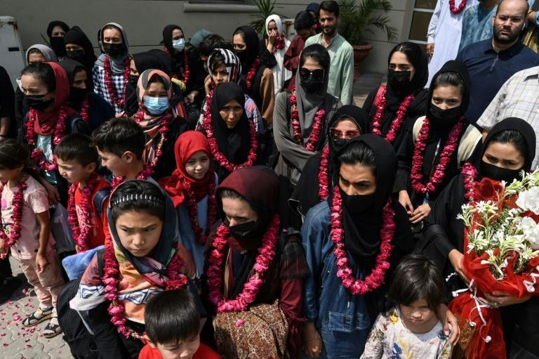 The team wore garlands as they arrived at the Pakistan Football Federation in Lahore (AFP/Arif ALI)