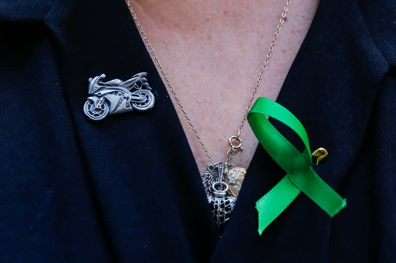 FILE PHOTO: A motorcycle pin is seen on the shirt of Charlotte Charles, the mother of British teen Harry Dunn who was killed in a car crash on his motorcycle, allegedly by the wife of an American diplomat, during an interview in the Manhattan borough of New York