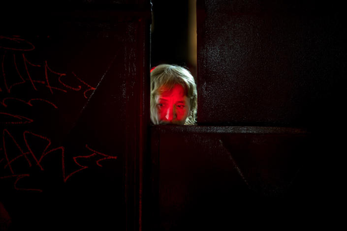 """FILE - In this Monday, Nov. 2, 2015 photograph, a woman's face is lit by candles placed outside the Colectiv nightclub as she peers from behind the metal gate leading to the club in Bucharest, Romania. The Oscar-nominated Romanian documentary film """"Collective"""" follows a group of journalists delving into the state of health care in the eastern European country in the wake of a deadly 2015 nightclub fire that left dozens of burned victims in need of complex treatment. What they revealed was decades of deep-rooted corruption, a heavily politicized system scarily lacking in care. (AP Photo/Vadim Ghirda, File)"""