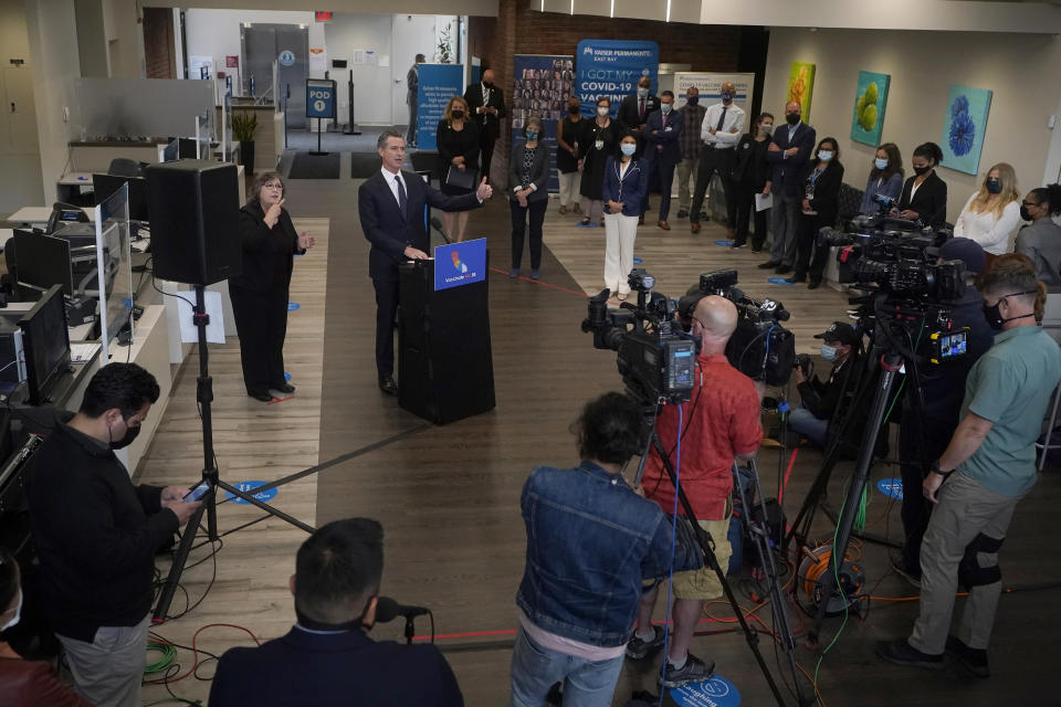 Gov. Gavin Newsom, middle left, speaks at a news conference in Oakland, Calif., Monday, July 26, 2021. California will require state employees and all health care workers to show proof of COVID-19 vaccination or get tested weekly. Officials are tightening restrictions in an effort to slow rising coronavirus infections in the nation's most populous state, mostly among the unvaccinated. (AP Photo/Jeff Chiu)