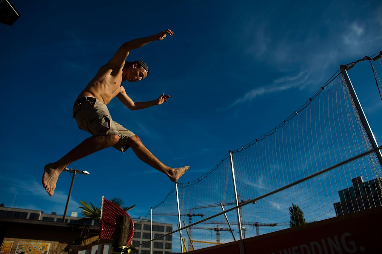 BERLIN, GERMANY - AUGUST 20:  Yorin, 23, performs on a slackline at the East Side Beach on August 20, 2011 in Berlin, Germany. Berlin, which is among Europe's most popular travel destinations, is crisscrossed with canals and rivers over which lead a total of 564 bridges. The city's ample access to water has encouraged many bar and restaurant owners to create beach atmosphere as a growing summer day- and nightlife institution.  (Photo by Carsten Koall/Getty Images)