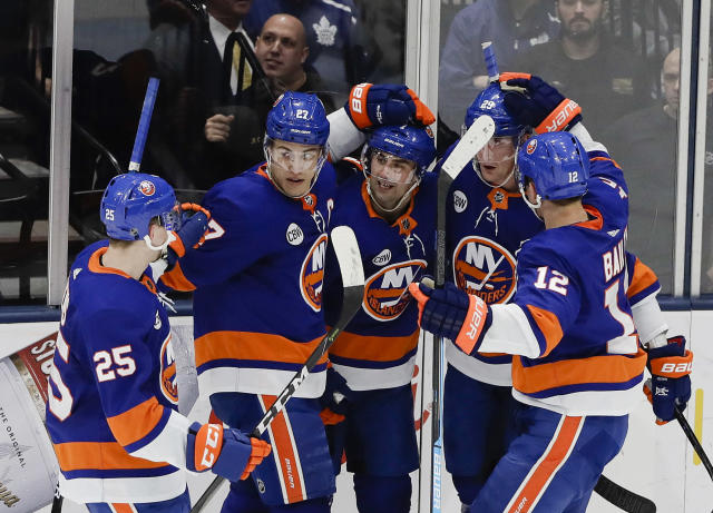 New York Islanders' Jordan Eberle, center, celebrates with teammates Devon Toews (25), Anders Lee (27), Brock Nelson (29) and Josh Bailey (12) during the third period of an NHL hockey game Monday, April 1, 2019, in Uniondale, N.Y. The Maple Leafs won 2-1. (AP Photo/Frank Franklin II)