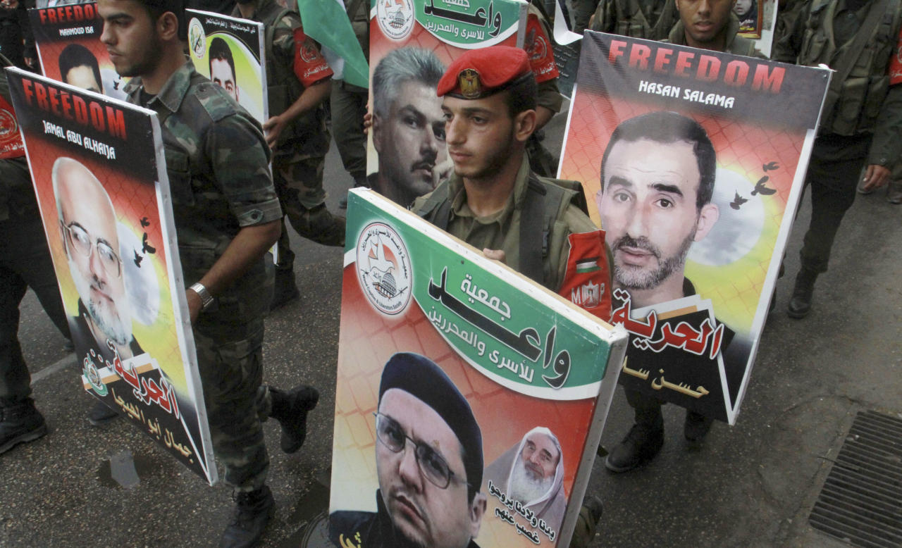 Palestinian Hamas police officers participate in a solidarity protest with Palestinian prisoners held in Israeli jails, on posters, in Gaza City, Monday, May 14, 2012. Hundreds of Palestinians are on a collective hunger strike in Israeli jails since mid-April 2012.(AP photo/Hatem Moussa)