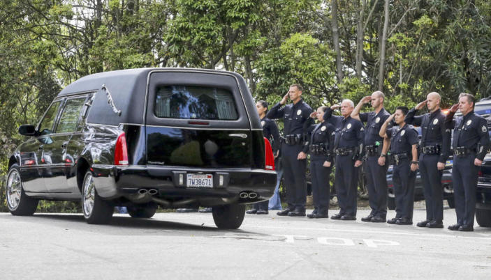 <p>Los Angeles police officers salute as a hearse leaves the home of Nancy Reagan in the Bel-Air district of Los Angeles on Sunday.<i> (Photo: Ringo H.W. Chiu/AP)</i></p>