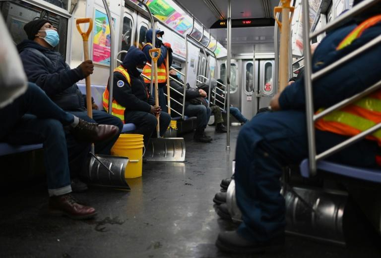 Workers hold snow shovels on the subway during a winter storm on February 1, 2021 in New York City