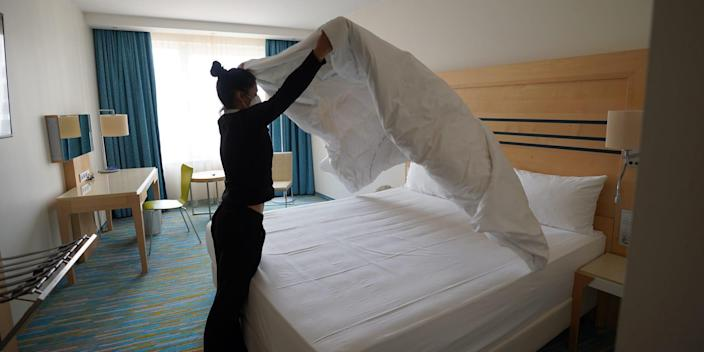 A woman makes a hotel bed