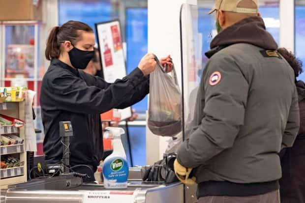 A cashier wearing a mask to help slow the spread of COVID-19. Nunavut announced Sunday that masks are now mandatory territory wide. (Natalie Maerzluft/Reuters - image credit)
