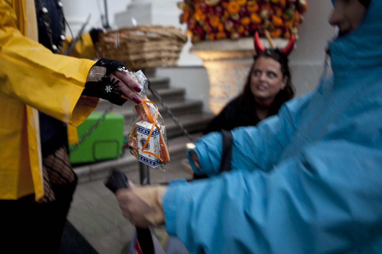 WASHINGTON - OCTOBER 29:  A volunteer gives a treat bag to a trick or treater at the White House October 29, 2011 in Washington, DC.  President Barack Obama and first lady Michelle Obama hosted military families and other trick or treaters for a Halloween party.  (Photo by Brendan Smialowski/Getty Images)