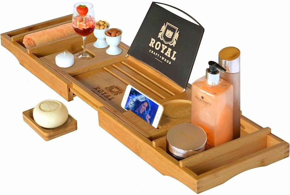 <p>I mean, how cool is this? Now you can read in the tub without worrying about drowning your reading material, thanks to this <span>Royal Craft Wood Luxury Bathtub Caddy Tray</span> ($55, originally $58). You can also bring in drinks and snacks, because self care.</p>
