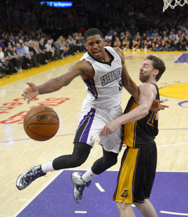 Sacramento Kings forward Rudy Gay, left, reaches for a loose ball along with Los Angeles Lakers center Pau Gasol, of Spain, during the first half of an NBA basketball game on Friday, Feb. 28, 2014, in Los Angeles. (AP Photo/Mark J. Terrill)