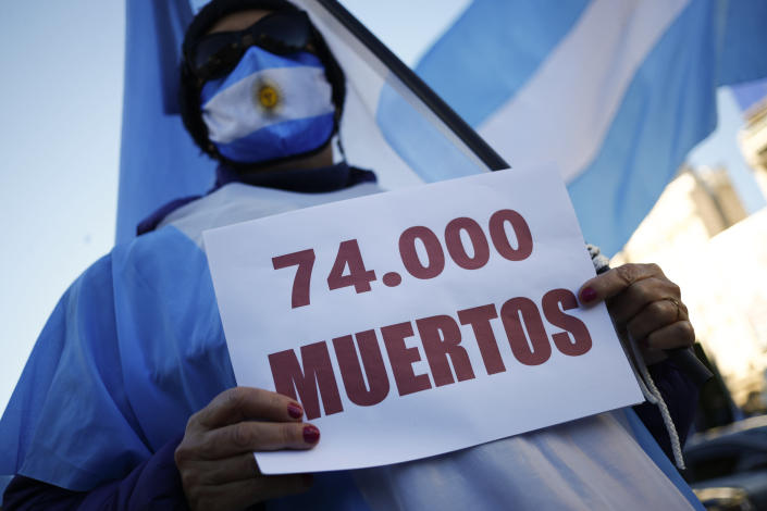 """A man holds a sign that reads in Spanish """"74.000 deaths"""" as he attends a protest against how the government of President Alberto Fernandez is handling the new coronavirus pandemic crisis, in Buenos Aires, Argentina, Tuesday, May 25, 2021. (AP Photo/Marcos Brindicci)"""