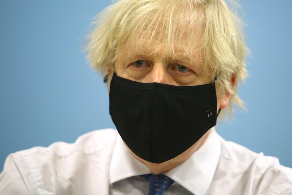 "CWMBRAN, WALES – FEBRUARY 17: British Prime Minister Boris Johnson wears a face mask with the number 10 on it during a visit to the vaccination centre at Cwmbran Stadium on February 17, 2021 in Cwmbran, Wales. The Prime Minister visited the vaccination centre to see the progress of the COVID-19 vaccine roll out in Wales. During the visit he explained that the lifting of the coronavirus lockdown would be ""based firmly on a cautious and prudent approach"". (Photo by Geoff Caddick – WPA Pool/Getty Images)"