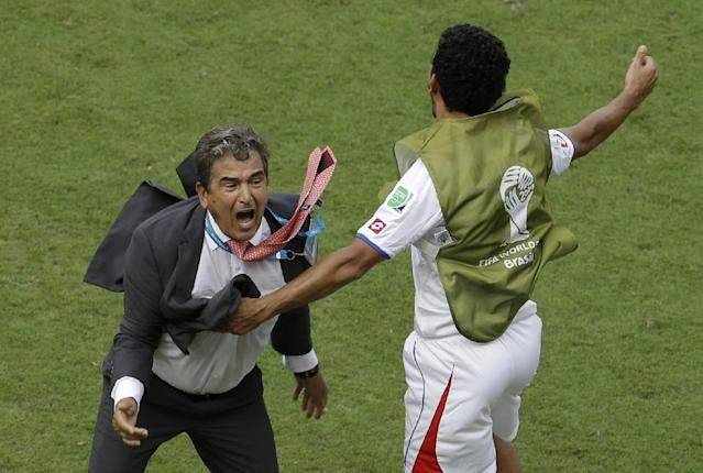 Costa Rica's head coach Jorge Luis Pinto, left, celebrates after winning 1-0 against Italy in the group D World Cup soccer match between Italy and Costa Rica at the Arena Pernambuco in Recife, Brazil, Friday, June 20, 2014. (AP Photo/Hassan Ammar)