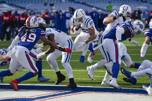 Indianapolis Colts' Jonathan Taylor (28) leaps into the end zone for a touchdown in front of Buffalo Bills' Tremaine Edmunds (49) during the first half of an NFL wild-card playoff football game Saturday, Jan. 9, 2021, in Orchard Park, N.Y. (AP Photo/Adrian Kraus)