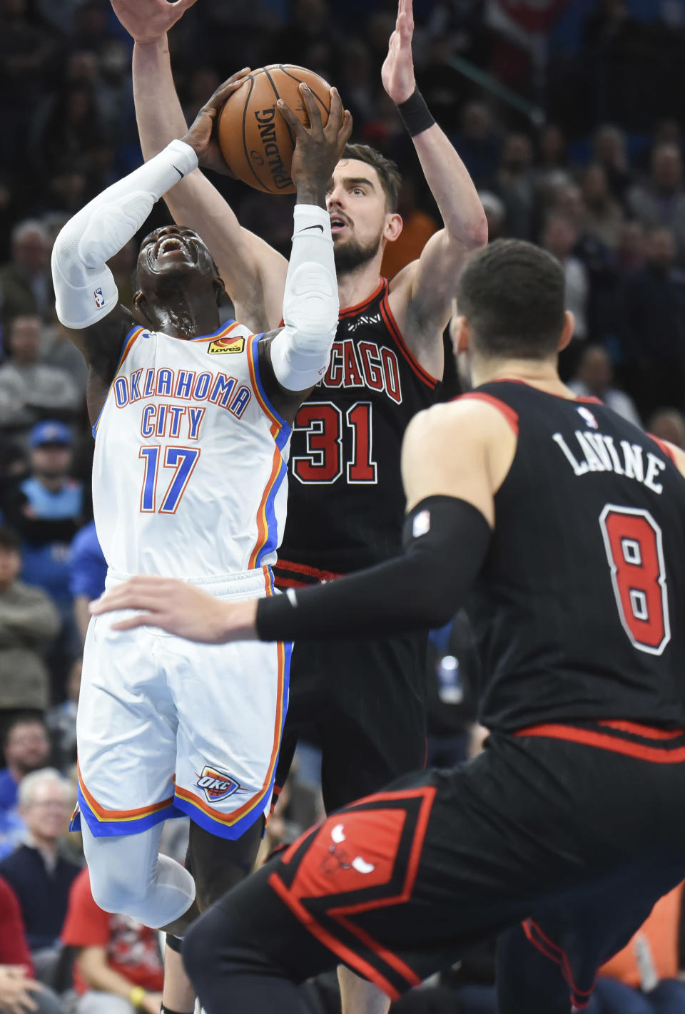 Oklahoma City Thunder guard Dennis Schroder (17)shoots the ball around Chicago Bulls guard Tomas Satoranksy (31) and Zach LaVine (8) in the second half of an NBA basketball game, Monday, Dec. 16, 2019, in Oklahoma City. (AP Photo/Kyle Phillips)