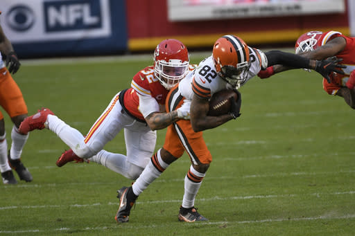 Cleveland Browns wide receiver Rashard Higgins (82) is tackled by Kansas City Chiefs safety Tyrann Mathieu (32) after catching a pass during the second half of an NFL divisional round football game, Sunday, Jan. 17, 2021, in Kansas City. The Chiefs won 22-17. (AP Photo/Reed Hoffmann)