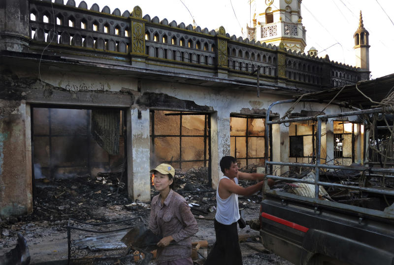 In this May 29, 2013 photo, Ma Sandar Soe, left, salvages goods from her burned shop in the foreground of a vandalized mosque in Lashio, northern Shan State, Myanmar. When a huge mob of Buddhist thugs crawled on the roof of Ma Sandar Soe's shop, doused it with gasoline and set it ablaze, the Buddhist businesswoman didn't blame them for burning it to the ground despite seeing it happen with her own eyes. Instead, her wrath was reserved for minority Muslims she accused of igniting Myanmar's latest round of sectarian unrest. (AP Photo/Todd Pitman)