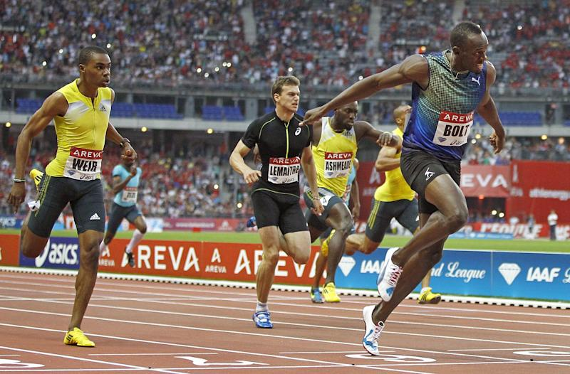 Jamaican sprinter Usain Bolt, right, stretches out to win the men's 200-meter race, during the Athletics Diamond League meeting at Stade de France stadium, in Saint Denis, north of Paris, Saturday, July 6, 2013. Other sprinters are from left: Jamaican Warren Weir, France's Christophe Lemaitre, Jamaican Nickel Ashmeade. (AP Photo/Remy de la Mauviniere)