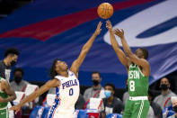 Boston Celtics guard Kemba Walker, right, shoots a 3-pointer over Philadelphia 76ers guard Tyrese Maxey during the first half of an NBA basketball game Wednesday, Jan. 20, 2021, in Philadelphia. (AP Photo/Chris Szagola)