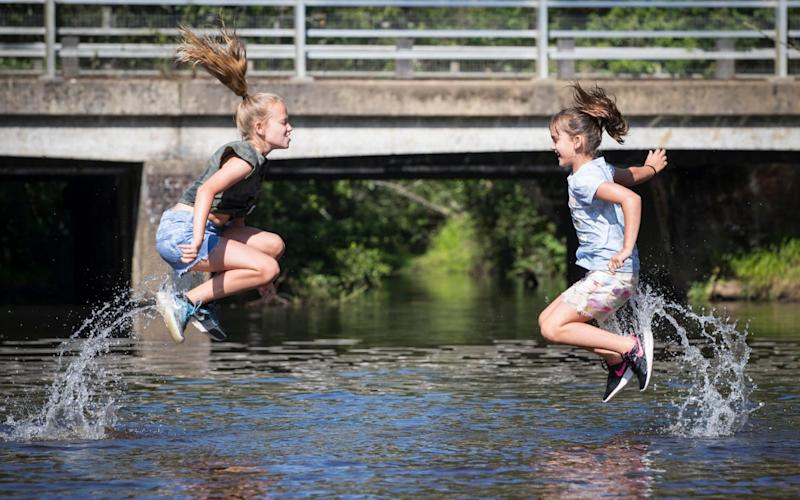 UK Weather: Sisters Ebony 11 and Isobella 8 cool off in the river at Brockenhurst in the New Forest as the hot weather continues across the UK - www.alamy.com