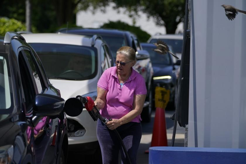 A customer pumps gas at Costco, as others wait in line, on Tuesday, May 11, 2021, in Charlotte, N.C. Gasoline futures are ticking higher following a cyberextortion attempt on the Colonial Pipeline, a vital U.S. pipeline that carries fuel from the Gulf Coast to the Northeast. (AP Photo/Chris Carlson)