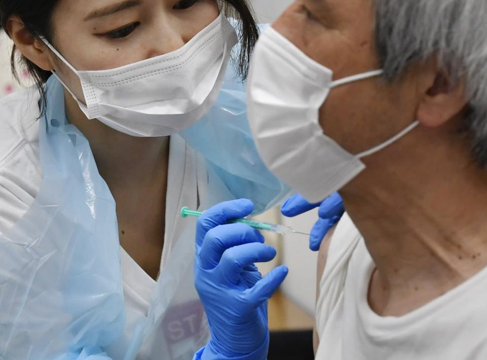 A man receives the Pfizer COVID-19 vaccine at the Noevir Stadium Kobe in Kobe, western Japan, Monday, May 31, 2021. The stadium is being used as an inoculation venue for local residents over 65 years old. Japan, seriously behind in coronavirus vaccination efforts, is scrambling to boost daily shots as the start of the Olympics in July closes in. (Yu Nakajima/Kyodo News via AP)