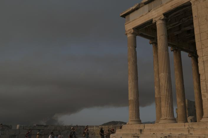 Tourists visit Acropolis hill as smoke from a wildfire north of the Greek capital, spreading over Athens, Greece, Tuesday, Aug. 3, 2021. Hundreds of residents living near a forest area north of Athens fled their homes Tuesday as a wildfire reached residential areas as Greece grappled with its worst heatwave in decades. (AP Photo/Aggelos Barai)
