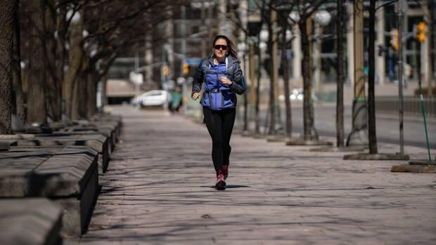 A runner makes her way alongside Major's Hill Park in downtown Ottawa on April 5, 2021. Outdoor exercise is still allowed under the provincial stay-at-home order. (Jean-Francois Benoit/CBC - image credit)