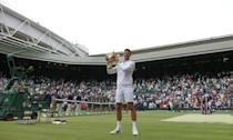 King and his court: Novak Djokovic holds the winner's trophy