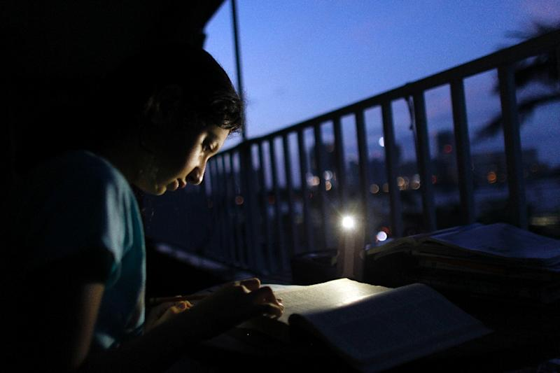 Alana Rivera, age 10, does her homework on her apartment's balcony, with only a cell phone for light (AFP Photo/Ricardo ARDUENGO)
