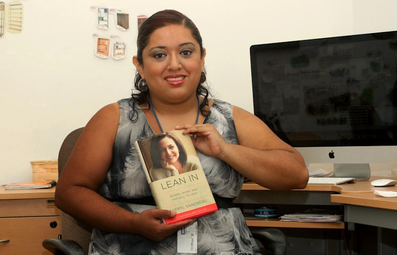 """In this Aug. 12, 2013 photo, marketing executive Ana Falcon poses with a copy of Facebook COO Sheryl Sandberg's book """"Lean In,"""" in Monterrey, Mexico. Falcon is working to set up a Lean In circle, or small empowerment group for working women. The circles are inspired by Sandberg's book, a manifesto for women in the workplace. Sandberg says that since the book was launched in March, more than 7,000 such circles have been formed, in all 50 states and in 50 countries. (AP Photo/Alfredo Lopez)"""