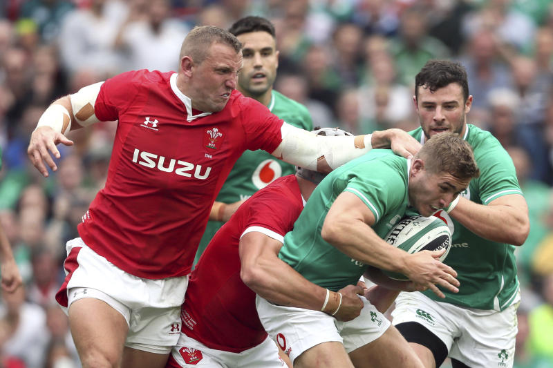 Ireland's Jordan Larmour is tackled by Wales' Jonathan Davies and Hadleigh Parke, left, during the summer series rugby match between Wales and Ireland at the Aviva Stadium, Dublin, Ireland, Saturday Sept. 7, 2019. (Brian Lawless/PA via AP)