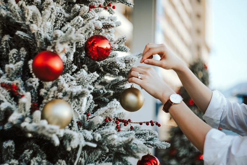 Cropped hand of woman decorating and hanging baubles on Christmas tree