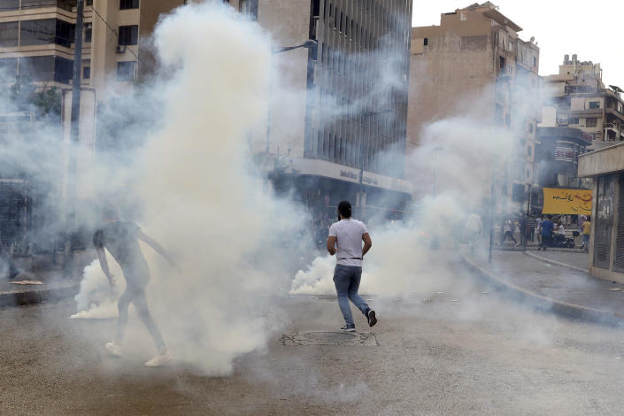 Protesters runs from the smoke of tear gas during a protest against French President Macron's comments over Prophet Muhammad caricatures, near the Pine Palace, which is the residence of the French ambassador, in Beirut, Lebanon, Friday, Oct. 30, 2020. A few hundred demonstrators held a protest called for by a Sunni Islamist party, Hizb ul-Tahrir, against French cartoons of the Prophet Muhammad. (AP Photo/Bilal Hussein)