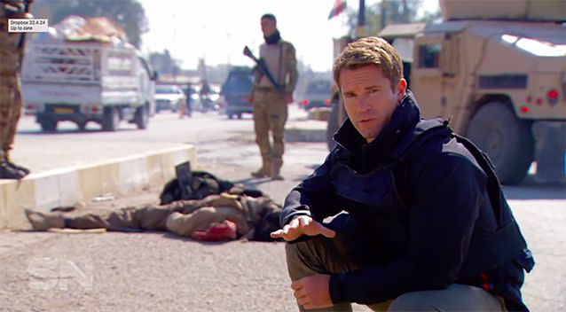Behind reporter Denham Hitchcock, three dead bodies lie on the street. It's a common sight in Mosul.