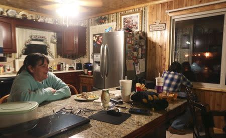 Brenda Manley (L), watches local news reports about a crude oil train fire as her husband, Dane (R), watches the train burn through a kitchen window in Boomer, West Virginia February 16, 2015. REUTERS/Marcus Constantino