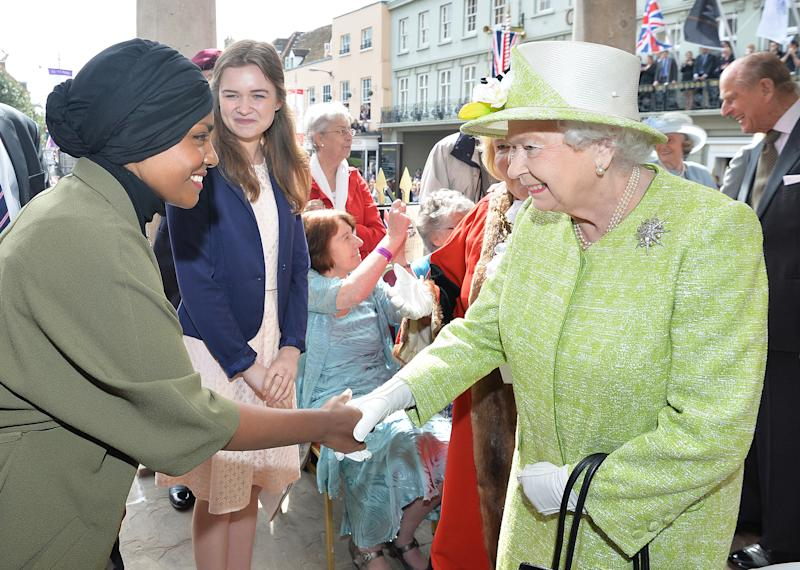 Britain's Queen Elizabeth II shakes hands with Nadiya Hussein (L), winner of the Great British Bake Off who baked a cake for her during a 'walkabout' on her 90th birthday in Windsor, west of London, on April 21, 2016. Britain celebrates Queen Elizabeth II's 90th birthday on Thursday, with her eldest son Prince Charles paying tribute in a special radio broadcast and Prime Minister David Cameron leading a parliamentary homage. / AFP / POOL / John Stillwell (Photo credit should read JOHN STILLWELL/AFP via Getty Images)
