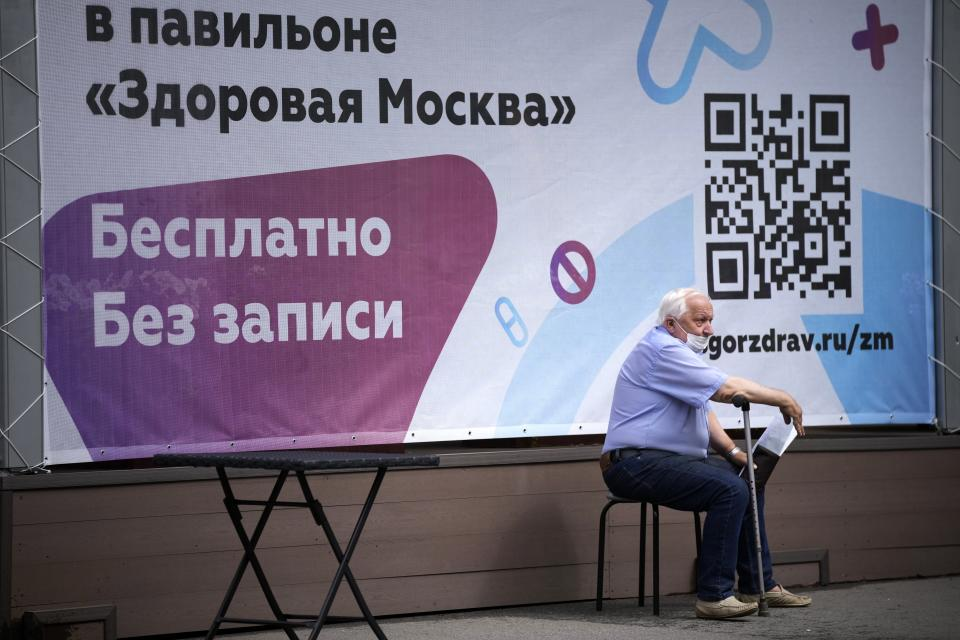 FILE - In this Friday July 2, 2021 file photo, a man waits for a coronavirus vaccine at a vaccination center at VDNKh (The Exhibition of Achievements of National Economy) with the QR code sign in the background in Moscow, Russia. Faced with worrying surges of coronavirus infections driven by the more transmissible delta variant, European nations have been scrambling to ramp up vaccination drives, using a mixture of stick-and-carrot measures to persuade the reluctant to get their shots. (AP Photo/Alexander Zemlianichenko, File)
