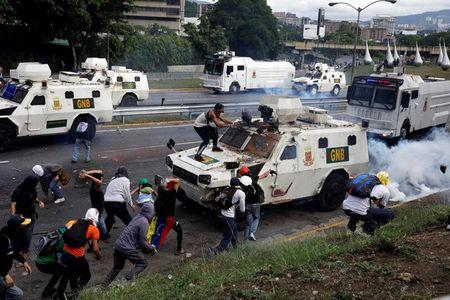 Demonstrators clash with riot police on armored car during rally against Venezuela's President Nicolas Maduro in Caracas