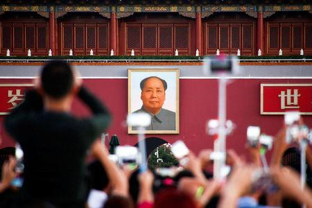 People take pictures during the flag raising ceremony on Tiananmen Square as the portrait of China's late Chairman Mao Zedong is seen in the background in Beijing, China, on the 40th anniversary of his death September 9, 2016. REUTERS/Thomas Peter
