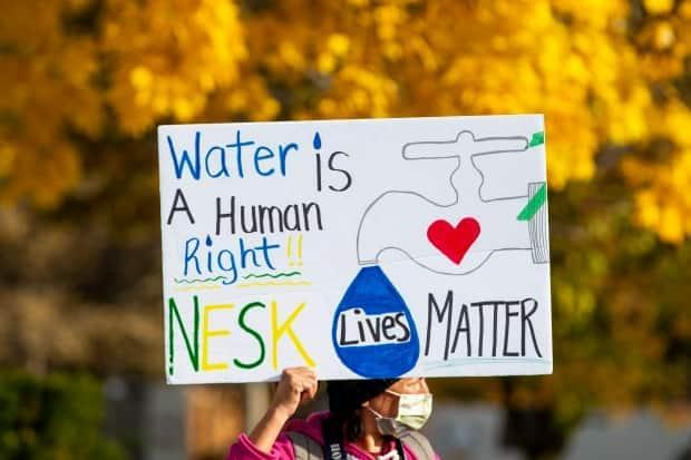 A sign is held up as people stand outside Queen's Park in Toronto on Nov. 6, 2020, in solidarity with the Neskantaga First Nation where residents were evacuated over tainted water a month earlier. (Carlos Osorio/The Canadian Press - image credit)