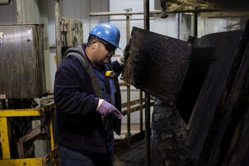 A Suncor oil worker checks an oil tank at the Suncor tar sands operations near Fort McMurray, Alberta, September 17, 2014. In 1967 Suncor helped pioneer the commercial development of Canada's oil sands, one of the largest petroleum resource basins in the world. (REUTERS/Todd Korol)