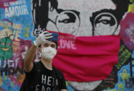 """A man takes a selfie by the """"Lennon Wall"""" with a face mask attached to the image of John Lennon, in Prague, Czech Republic, Monday, April 6, 2020. The Czech Republic's government has incorporated dramatic restrictive measures to try and stem the spread of the new coronavirus. (AP Photo/Petr David Josek)"""